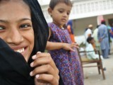 A shy girl smiles as aid is distributed in the school where her family has temporarily taken shelter PHOTO: MEHEK ASAD