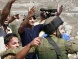 An Israeli soldier stops Palestinians at a check post PHOTO: AFP