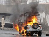 A man walks past a rickshaw on fire during a fresh wave of violence in the port city of Karachi on July 14, 2011. PHOTO: AFP
