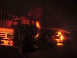A firefighter distinguishes flames rising from a truck in Karachi early July 14, 2011. PHOTO: AFP
