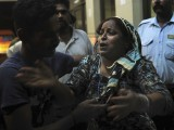 A man tries to comfort a relative of a injured victim at a hospital in Karachi early July 14, 2011. PHOTO: AFP