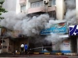 Fire fighters work to extinguish a fire in a shop set on fire during a fresh wave of violence in Karachi on July 14, 2011. PHOTO: AFP