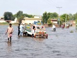 The flood victims of Badin try to navigate their way through the inundated roads. PHOTO: YOUSUF NAGORI