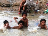 Children splash around in the puddles that gathered after heavy rainfall in Karachi. PHOTO: RASHED AJMER/EXPRESS
