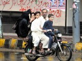 Families enjoy the pleasant weather and go for drives during the rain. PHOTO: MUHAMMED AZEEM/EXPRESS