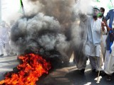 Supporters of Malik Mumtaz Hussain Qadri burn tyres, after the court announced the death sentence for Qadri, outside Adiyala Prison in Rawalpindi on October 1, 2011. PHOTO: AFP