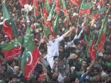 The throngs of people and the sea of red-green flags waving in unison to patriotic songs in Karachi at the recent PTI jalsa was a sight to behold. PHOTO: REUTERS