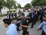 Security personal escort Prime Minister YousAf Raza Gilani's car as he leaves the Supreme Court. PHOTO: AFP