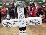 A cross is inscribed at a memorial for victims behind the theater. PHOTO: REUTERS