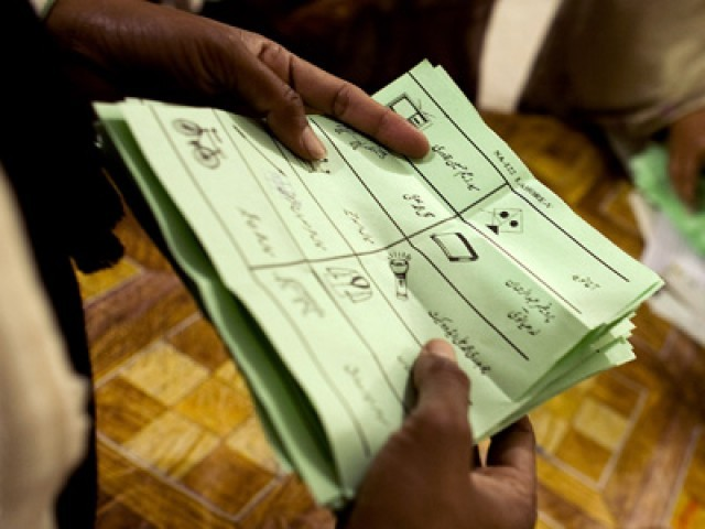 An election worker count ballots at a polling station for Pakistan's general elections in Lahore