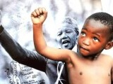 A young member of the Maitibolo Cultural Troupe poses in front of a photograph of Nelson Mandela outside the Medi Clinic Heart Hospital, where the anti-apartheid icon is admitted. PHOTO: AFP