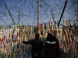 A family looks at a military fence decorated with ribbons, on which people have written their hopes for peace and reunification of the divided Korean peninsula, near the demilitarised zone separating the two Koreas, in Paju. PHOTO: REUTERS