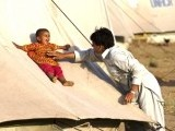 A displaced Pakistani man plays with his baby in Chota Lahore camp at Swabi district. PHOTO: AFP