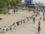 IDPs, fleeing a military operation in the North Waziristan tribal agency, wait in line outside a World Food Programme aid distribution centre in Bannu. PHOTO: AFP