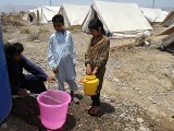 Internally displaced Pakistani children fill their buckets with water at a makeshift refugee camp in Bannu. PHOTO: AFP