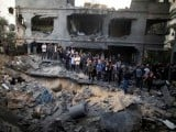 Palestinians gather around a destroyed house after an Israeli air strike in Gaza City. PHOTO: REUTERS