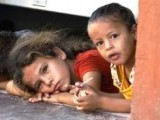 Displaced Palestinian children peak from under a shop door, where their family is taking shelter in Gaza City. PHOTO: AFP