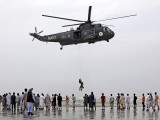 A Pakistan Navy helicopter carries out a search operation at Clifton beach. PHOTO: REUTERS
