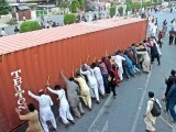 Supporters of Dr Tahirul Qadri push aside a shipping container blocking access to the leader's residence in Lahore. PHOTO: EXPRESS/SHAFIQ MALIK