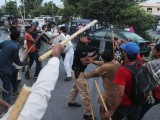 Police officials holding riot shields clash with PAT activists armed with sticks clash in Lahore. PHOTO: SHAFIQ MALIK/EXPRESS