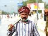 A Pakistani supporter of cleric Tahir-ul-Qadri walks near the Benazir Bhutto International Airport as others gather outside it in Islamabad on June 23, 2014. PHOTO: AFP