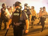 Police advance through a cloud of tear gas toward demonstrators protesting the killing of teenager Michael Brown in Ferguson. PHOTO: AFP