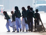 School children cross a road as they move away from the school that has been under attack. PHOTO: REUTERS