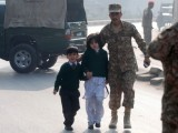 A soldier escorts school children after they were rescued from the Army Public School. PHOTO: REUTERS