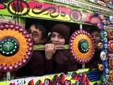 Schoolchildren inside a decorated van as they head to their school after it reopened in Peshawar. PHOTO: REUTERS