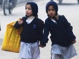 Girls carry their school bags as they walk along a road while heading to their school after it reopened in Peshawar. PHOTO: REUTERS