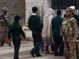 Soldiers stand guard as children arrive with their parents at the Army Public School in Peshawar on January 12, 2015. PHOTO: AFP