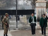 Pakistani soldiers stand guard as students leave. PHOTO: AFP