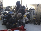 A Rangers soldier displays weapons recovered during a raid on the MQM's headquarters in Karachi. PHOTO: REUTERS