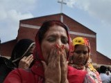Pakistani Christian women mourn as they gather at a church damaged from a suicide bombing attack in Lahore, Pakistan, Sunday. PHOTO: AP