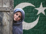 A Pakhtun girl stands at the doorway to her family dwelling in the outskirts of Peshawar on July 10, 2012. PHOTO: REUTERS