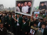 Students hold photographs of their schoolmates killed in an attack by Taliban gunmen on APS, during a protest in Peshawar. PHOTO: REUTERS