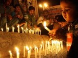 A boy lights a candle at a vigil for victims of Safoora Chowrangi attack. PHOTO: ONLINE