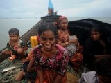 Rohingya Muslims, who tried to cross the Naf river into Bangladesh to escape sectarian violence in Myanmar, look on from an intercepted boat in Teknaf. PHOTO: AFP