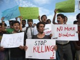 Pakistani civil society activists carry placards as they shout slogans during a protest against the killing of the Shiite Ismaili minority. PHOTO: AFP