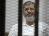 Egypt's deposed president Mohamed Morsi sits behind the defendants cage during a trial at the police academy court in Cairo on Nov 5, 2014.  PHOTO: AFP