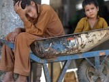 Pakistani boys sitting in a wheelbarrow wait for customers at a food market in Islamabad. PHOTO: AFP