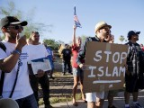 "A demonstrator shouts and carries a ""Stop Islam"" sign while another rips pages out of a Quran during a ""Freedom of Speech Rally Round II"" outside the Islamic Community Center of Phoenix, Arizona on May 29, 2015. PHOTO: REUTERS"