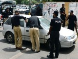 Pakistani policemen search a vehicle at a checkpoint in Karachi. PHOTO: AFP
