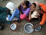 Pakistani girls affected by the floods wait for their daily ration of food at an army relief camp in Sultan Colony in Muzaffargarh distric of Punjab. PHOTO: AFP
