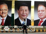 A policeman stands guard next to giant portraits of (L-R) Pakistan's President Mamnoon Hussain, China's President Xi Jinping, and Pakistan's Prime Minister Nawaz Sharif, displayed along a road ahead of Xi's visit to Islamabad April 19, 2015. PHOTO: REUTERS