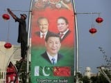 A man hangs decorations on a pole next to a banner showing Pakistan's President Mamnoon Hussain (L), China's President Xi Jinping (C) and Pakistan's Prime Minister Nawaz Sharif, ahead of Xi's visit to Islamabad April 19, 2015. PHOTO: REUTERS