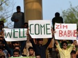 Pakistani spectators carry placards as they await the start of the first International T20 cricket match between Pakistan and Zimbabwe at the Gaddafi Cricket Stadium in Lahore on May 22, 2015. PHOTO: AFP