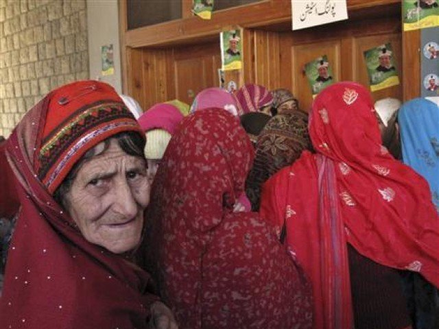 A woman stands in a queue to cast her vote during an election of the Legislative assembly for Northern Areas in Gilgit-Baltistan
