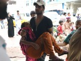 A man carries a heatwave victim to a hospital in Karachi on June 22, 2015.  PHOTO: AFP