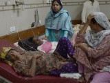 Relatives tend to heatstroke victims as they are treated at a government hospital in Karachi. PHOTO: AFP